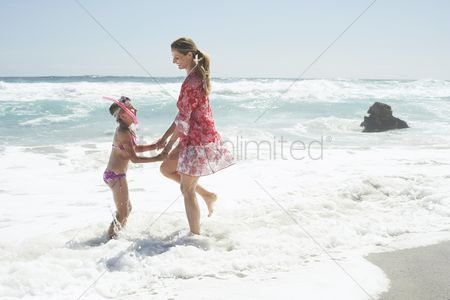 Children : Mother and daughter paddling on beach