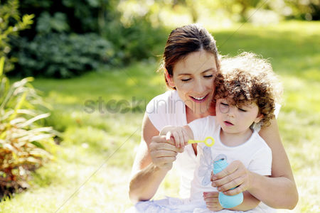 Grass : Mother and daughter playing with soap bubbles