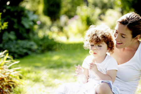 Enjoying : Mother and daughter playing with soap bubbles