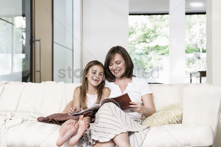 Daughter : Mother and daughter reading book in living room portrait