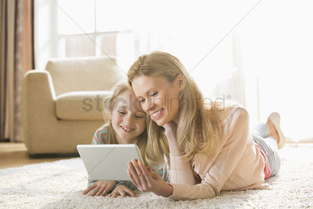 Love : Mother and daughter using digital tablet on floor at home