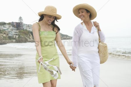 Daughter : Mother and daughter walk along beach holding hands