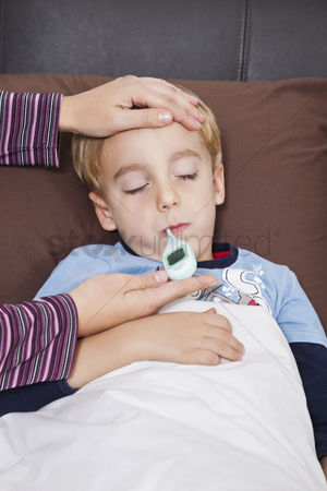 Thermometer : Mother checking unwell little boy s temperature with thermometer