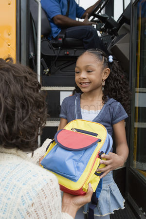 Women group outside : Mother handing daughter backpack on school bus