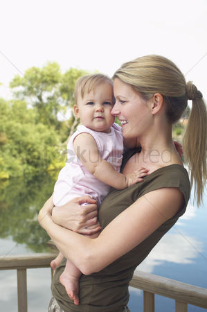 Ponytail : Mother holding daughter by lake half length