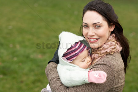 Closeness : Mother in park holding sleeping baby