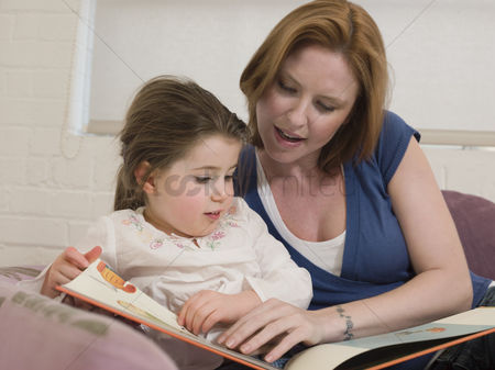 Girls : Mother reading to daughter