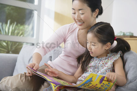 Asian : Mother sitting with daughter on sofa reading a book