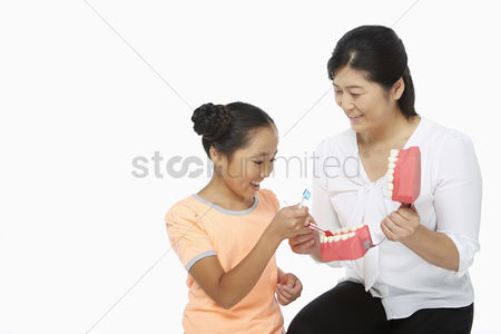 Tooth brush : Mother teaching daughter how to brush teeth