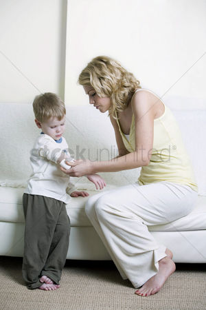 Medication : Mother wrapping son s arm with bandage