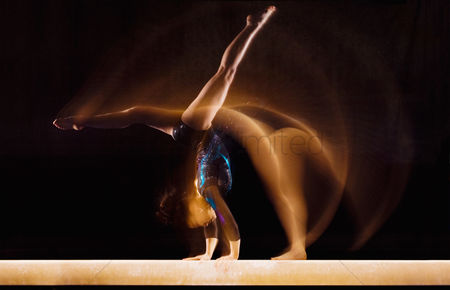 Black background : Multiple exposure image of female gymnast in motion on balance beam