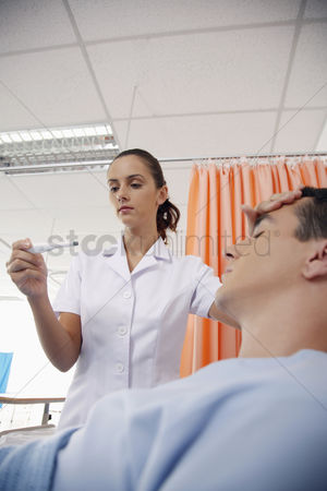 Thermometer : Nurse checking man s temperature