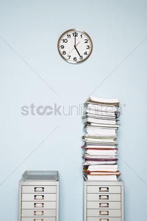 Pressure : Office wall with clock stack of paperwork in outbox on file cabinet