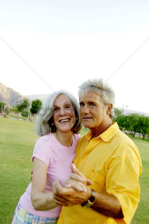 Aging process : Old couple dancing in the park