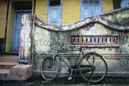Transportation : Old fashioned bicycle left by crumbling wall