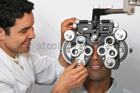 Examination : Optician performing eye test on patient