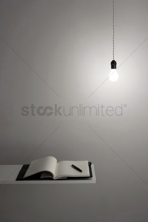 Examination : Organizer and pen on a plank with light bulb hanging from the top