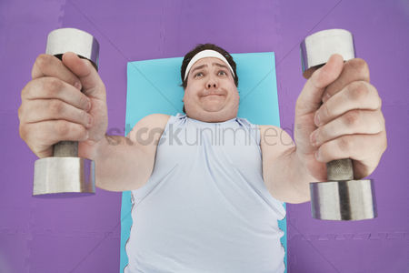 Worry : Overweight man lying down lifting dumbbells overhead view