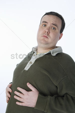 Ache : Overweight mid-adult man with hands on his belly