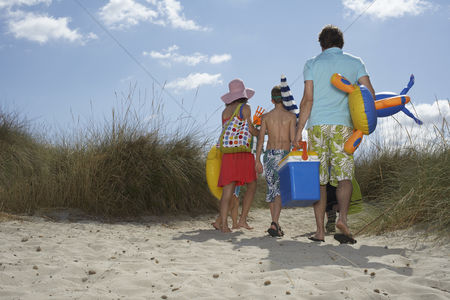 Toy : Parents and three children  6-11  carrying beach accessories back view