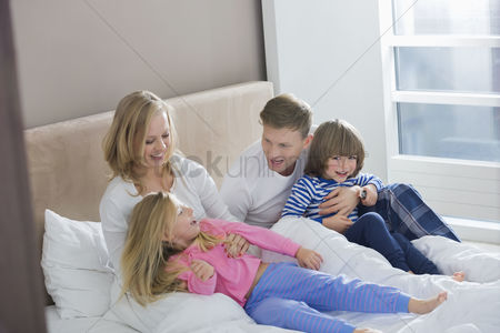Children : Parents playing with children in bedroom