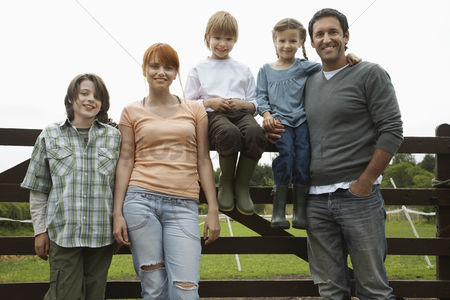 Pocket : Parents with three children  5-9  by fence in countryside portrait