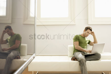 One man only : Pensive man using laptop on modern sofa in modern apartment
