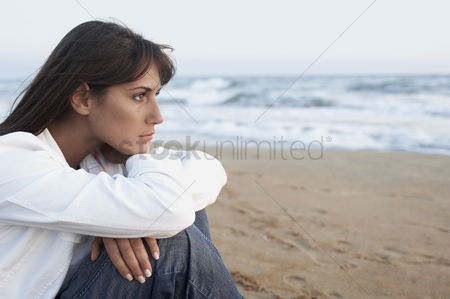 Contemplation : Pensive woman on the beach looking out to sea side view close up