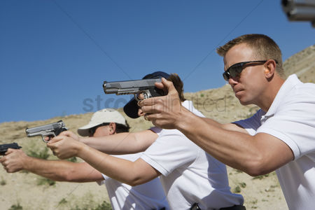 Firing : People aiming hand guns at firing range
