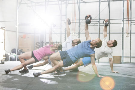 Sports : People exercising with kettlebells at crossfit gym