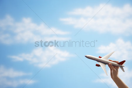 Transportation : Person holding model airplane against sky