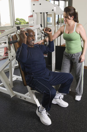 Client : Personal trainer working with senior man