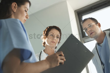 Relationships : Physicians reviewing medical chart low angle view