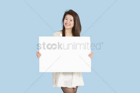 Cardboard cutout : Portrait of a beautiful young woman holding blank cardboard over blue background
