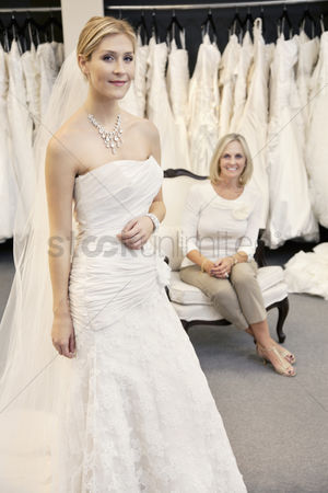 Offspring : Portrait of a beautiful young woman in wedding dress with mother sitting background
