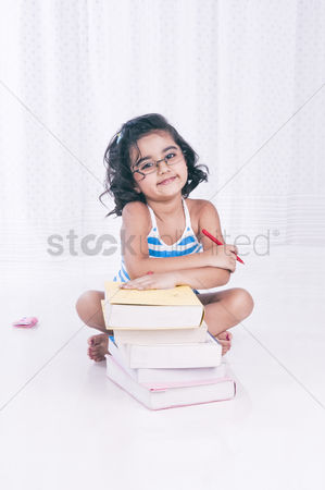 Bliss : Portrait of a girl sitting near books and smiling