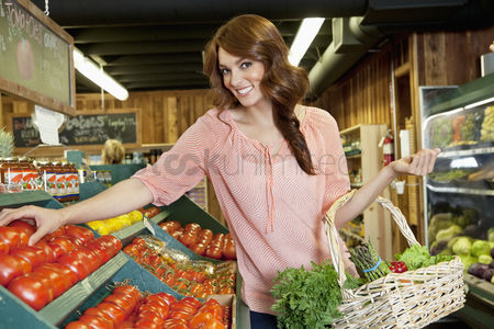 Shopping : Portrait of a happy brunette shopping for tomatoes in supermarket
