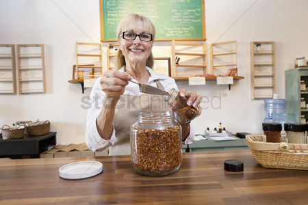 Employee : Portrait of a happy female employee pouring spice with scoop in jar