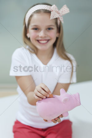 Czech republic : Portrait of a happy girl putting coin in piggy bank