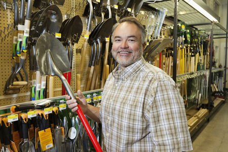 Employee : Portrait of a happy mature man holding shovel in hardware store