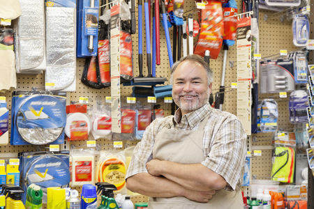Employee : Portrait of a happy mature salesperson with arms crossed in hardware store