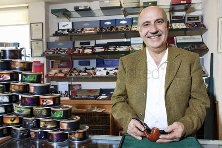 Business suit : Portrait of a happy mature tobacco shop owner with cans on display