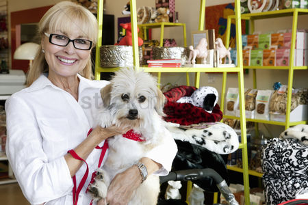 Large group of animals : Portrait of a happy senior woman carrying dog in pet shop