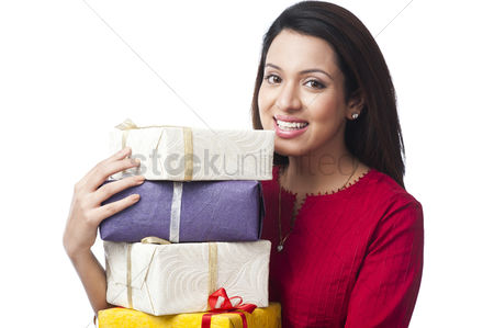 Housewife : Portrait of a happy woman holding a stack of gifts