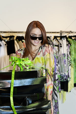 Spending money : Portrait of a happy woman wearing sunglasses while carrying clothes boxes in fashion store