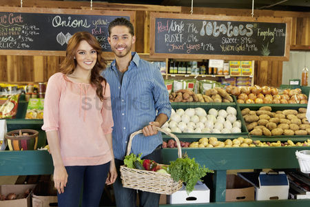 Supermarket : Portrait of a happy young couple in vegetable market