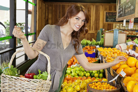 Shopping : Portrait of a happy young female shopping for fruits in market