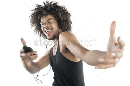 Portability : Portrait of a happy young man in vest dancing to tunes of mp3 player over white background