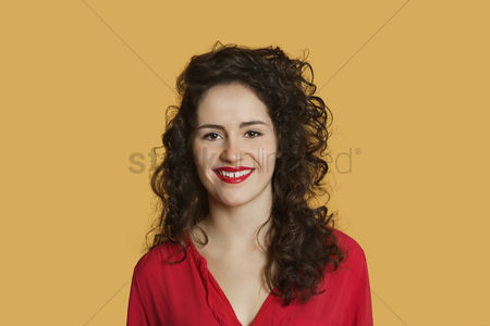 Curly hair : Portrait of a happy young woman with curly hair over colored background