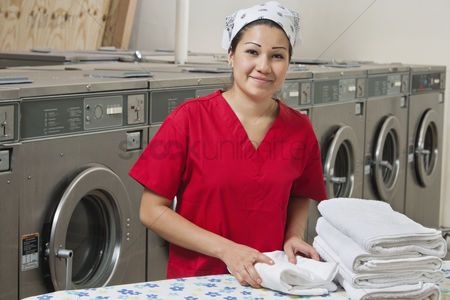 Employee : Portrait of a hispanic female employee with towel in laundromat